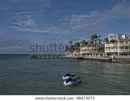 New apartment buildings condominiums on the beach in Key West. There is a pair of water craft waiting for passengers. - stock photo