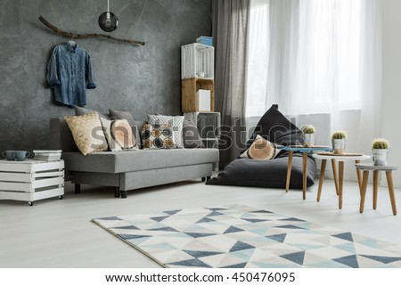 New Apartment Interior In Grey With Sofa, Modern Pouf, Small Table, Two  Chairs