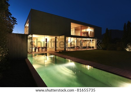 New architecture, beautiful modern house outdoors at night - stock photo