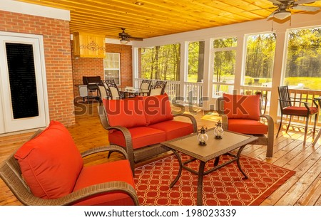 New backyard deck with fireplace overlooking lake with furniture - stock photo