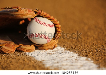New Baseball in a Glove in the Infield - stock photo