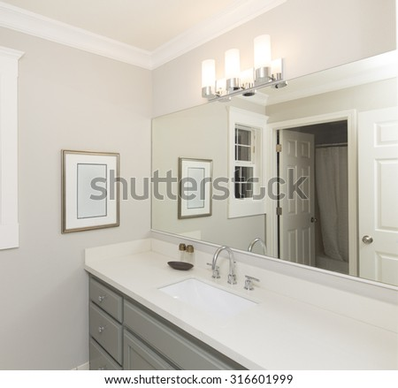 New bathroom with white sink, large mirror and marble counter top.  - stock photo