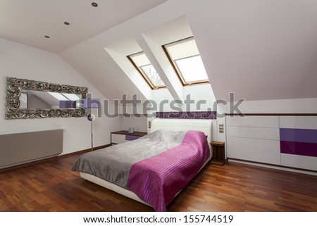 New bedroom with huge bed and purple additions - stock photo