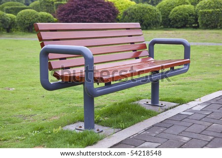 New bench on green grass in a park - stock photo