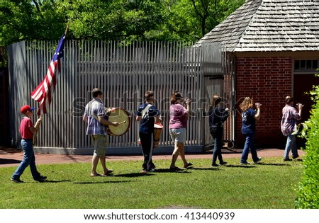 New Bern, North Carolina - April 24, 2016:  Sunday afternoon Fife and Drum corps with flag bearer marching in the gardens at 1770 Tryon Palace