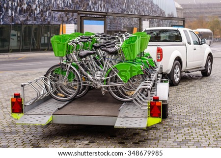 New bicycles with green accessories being transported on a trailer drawn by a pickup van on a cobbled street . view from the back of the bikes - stock photo