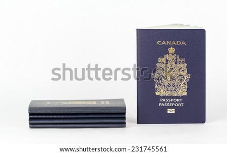 New biometric Canadian ePassport beside stack of old passports. - stock photo