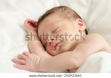 New born baby boy sleeping. Little baby taking a nap in white sheets. - stock photo