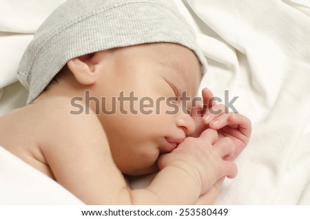 New born baby boy sleeping. Little baby with cute gray hat taking a nap.