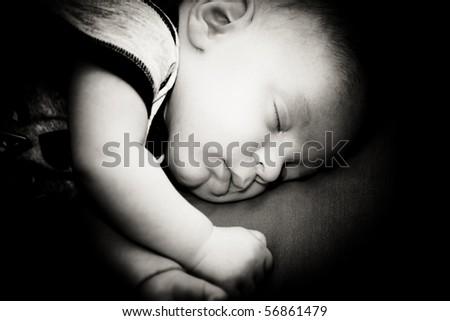 New born baby boy sleeping peacefully, black and white photograph. - stock photo