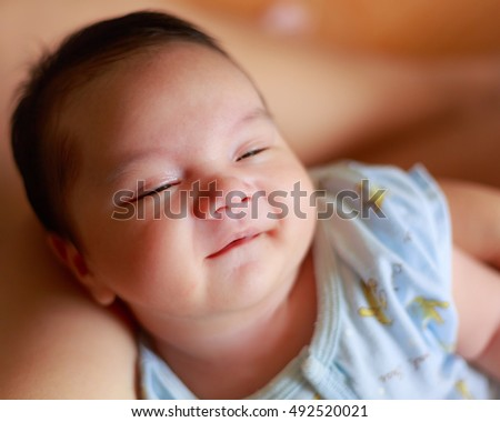 new born baby boy sleeping, smile on mother's arm