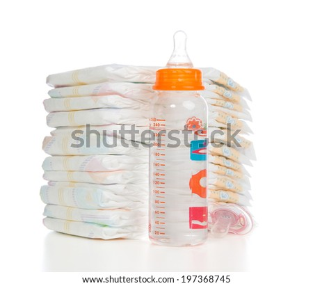 New born baby child stack of diapers, nipple soother, baby feeding milk bottle with water on a white background - stock photo