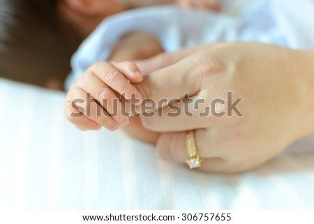 New born baby hand hoding hand's mother with burry wedding ring - stock photo