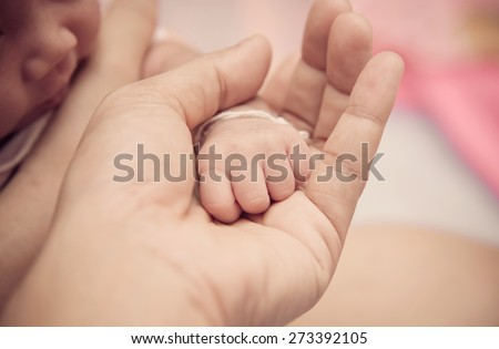 New born baby hand in mom's palm. - stock photo