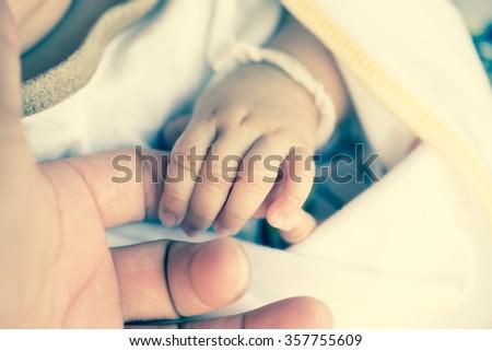 New born baby hand,vintage tone style - stock photo