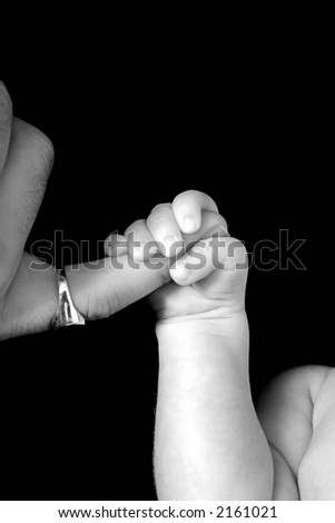 New born Baby holding dad's finger on black