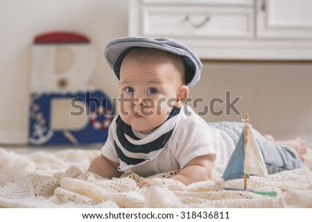 New born baby in a nautical vintage designed room and clothes - stock photo
