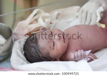 New born baby in doctor's hands - stock photo