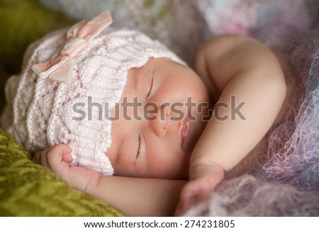 new born baby is lying and sleeping in colored shawl, sleeping baby, eyes closed, pink hat with bow - stock photo