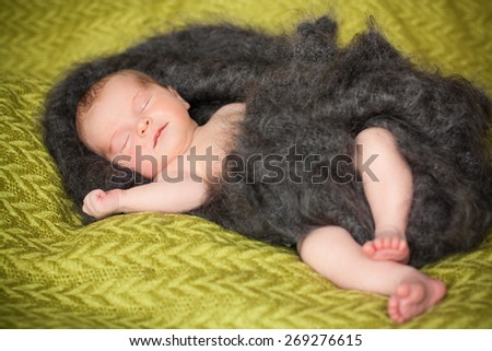 new born baby is lying in downy shawl, sleeping baby, eyes are closed - stock photo
