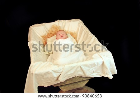 New Born Baby Jesus in a Manger: A Nativity Scene with a Real Child Isolated Over Black - stock photo