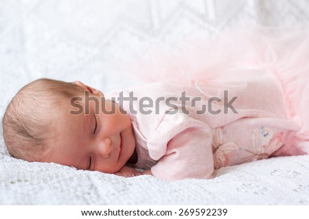 new born baby lying on texture blanket, light pink dress with bow-knot on back and  fluffy skirt - stock photo