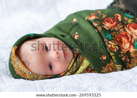new born baby lying on texture blanket wrapped in colored shawl with flowers, looking at camera, swaddled in shawl - stock photo