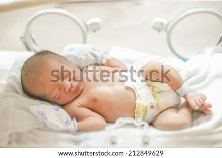 New born baby sleep in incubator. - stock photo