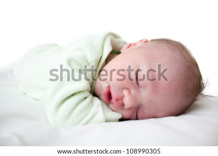 New born baby sleeping on he's arms and on a white bed. There is white copy space above him. - stock photo