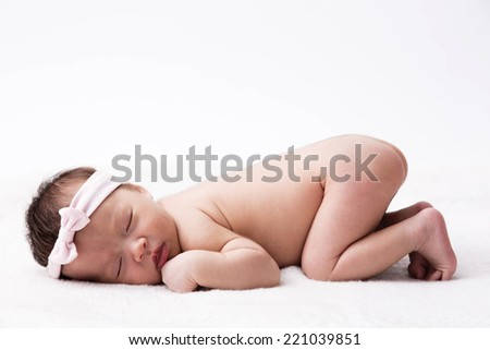 New born baby sleeping with pink head band