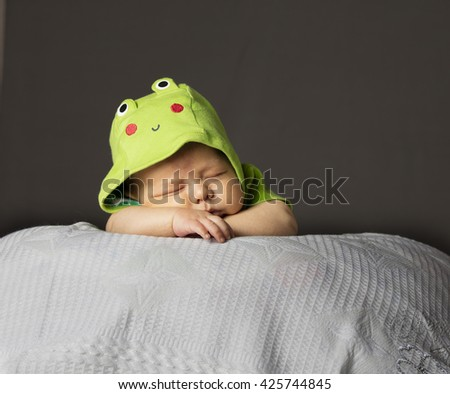 New Born Baby Sleeping wth green dress on white blanket - stock photo