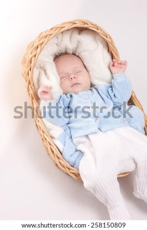 New born baby sleeps in basket with towel on white - stock photo