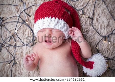 New born baby wearing a Santa hat and laying on the carpet, surrounded by fairy lights.   - stock photo