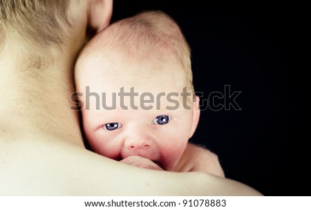 New Born Baby with Bright Blue Eyes Looking Over Father's Shoulder - Isolated over Black - stock photo