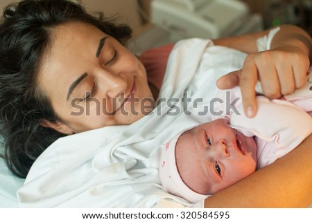 New born baby with mother in hospital - stock photo