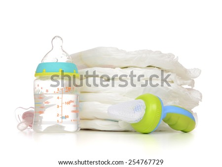 New born child stack of diapers nipple soother baby feeding milk bottle with water on a white background - stock photo