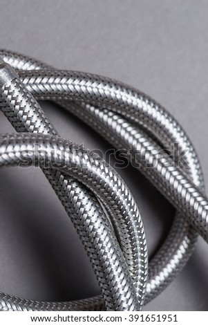 New braided stainless steel water hose over grey background