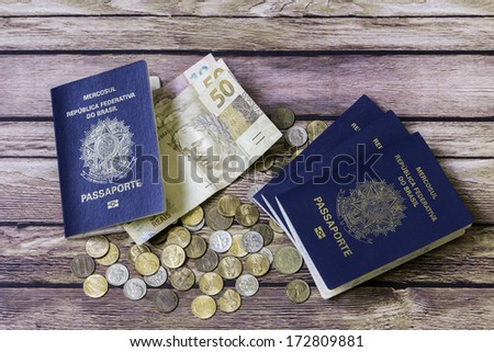 New Brazilian Passport, brazilian money and some American coins on the wooden table - stock photo