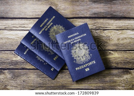 New Brazilian Passport on the wooden table - stock photo