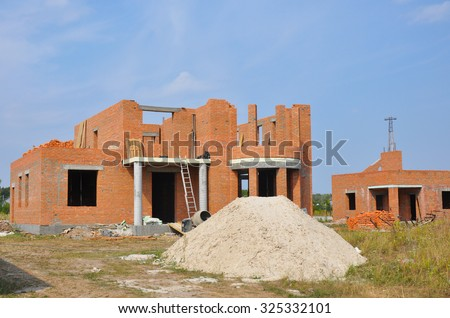New brick building house construction with doorway columns, windows, balcony - stock photo