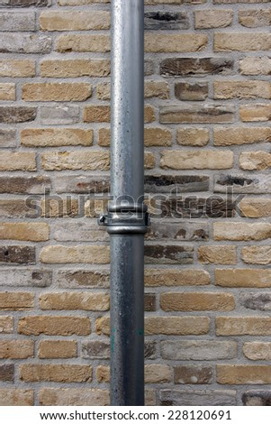 New brick wall with downspout. - stock photo