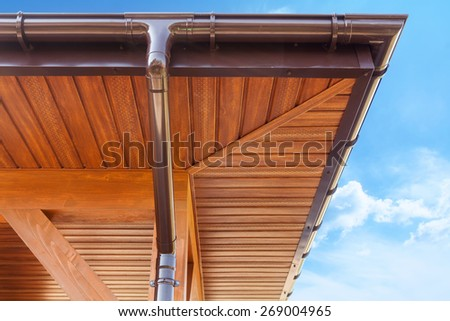 New brown copper gutter under a cloudy blue sky - stock photo