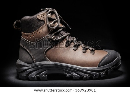 New brown waterproof hiking boot. Isolated on black background - stock photo