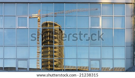 New build construction reflect in the windows of public building - stock photo