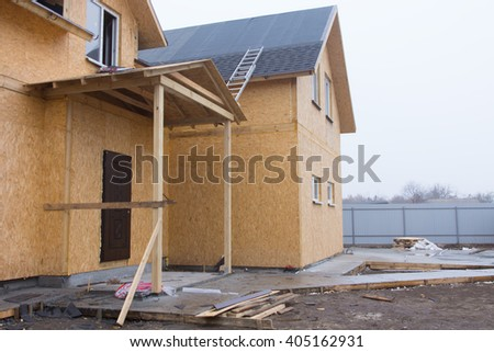 New build wooden house under construction with a ladder lying across the roof to install the tiles and a muddy forecourt waiting to be landscaped - stock photo