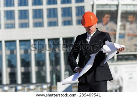 New building project fail. Young professional architect in protective helmet is furious because of mistake in blueprints. Business architects concept