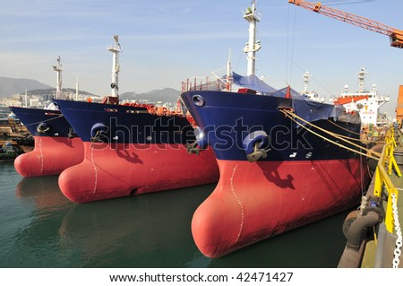 New building tankers in shipyard with cranes on background - stock photo