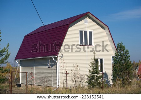 New built country house with red roof of metal tile and covered with beige siding on sunny day - stock photo