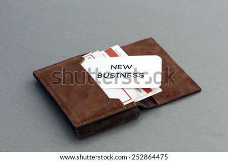 """New business. Conceptual composition with leather business-card folder, stack of colorful business cards and white business card with phrase """"New Business"""" on the foreground - stock photo"""