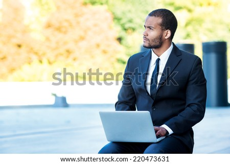 New businesses. African man businessman holding a laptop on his knees and looking away while sitting outside in the formal wear. - stock photo